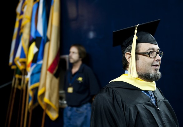 A Michigan graduate walks out of the tunnel and enters the Crisler Center floor on Sunday. Daniel Brenner I AnnArbor.com
