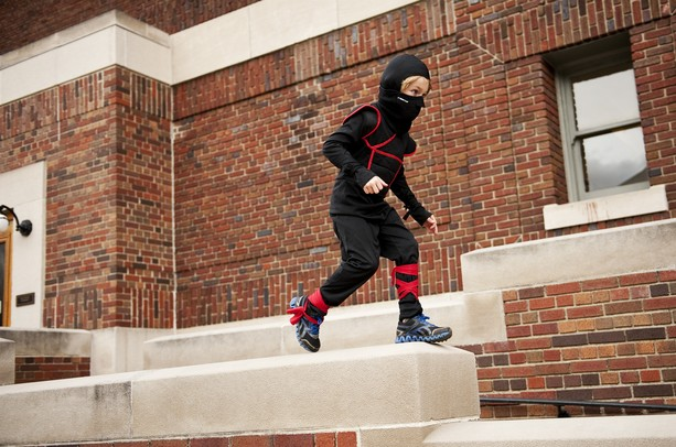 Oskar Roxstrom, seven, runs along a wall dressed as a ninja before the University of Michigan halloween concert on Sunday. Daniel Brenner I AnnArbor.com