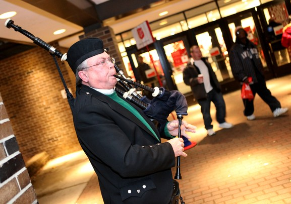 "Paul Kreger of the Detroit Caledonian Pipe Band plays for customers outside of Macy's department store as Santa Claus' bus tour stopped in at the Macy's in Briarwood Mall Tuesday  December 6, 201. ""We sent someone out because we want to welcome Santa,"" said Kreger. The purpose of the bus tour is to raise awareness of Macy's Believe campaign, which benefit?s Make-A-Wish.  Jeff Sainlar I AnnArbor.com"